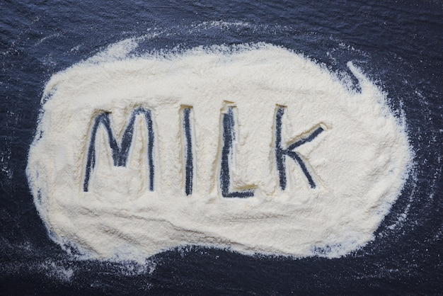 Milk powder on dark background - powdered milk text top view food healthy body from protein or for baby concept