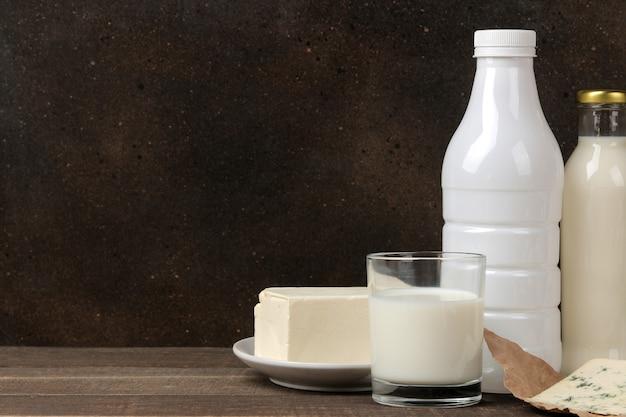 Молочные продукты. молоко, сметана, сыр, масло и творог на коричневом деревянном столе. место для текста