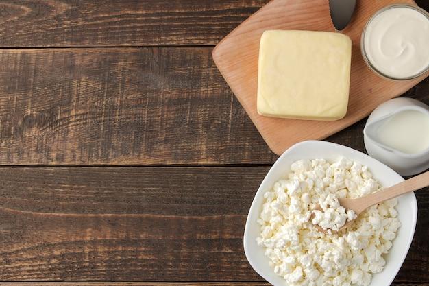 Молочные продукты. молоко, сметана, сыр, масло и творог на коричневом деревянном столе. вид сверху. рамка. место для текста