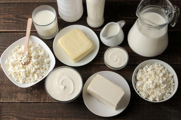 Молочные продукты. молоко, сметана, сыр, масло и творог на коричневом деревянном столе. вид сверху