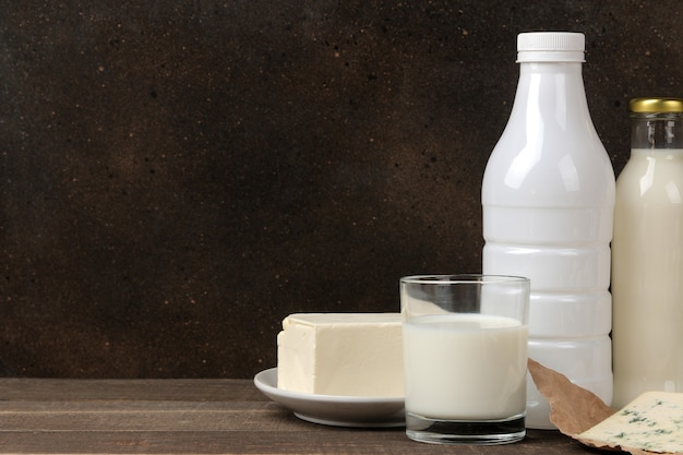 Milk products. milk, sour cream, cheese, butter and cottage cheese on a brown wooden table. space for text