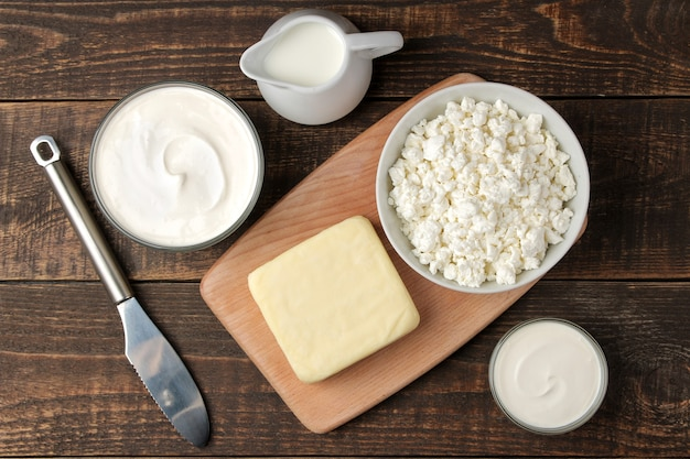 Milk products. milk, sour cream, cheese, butter and cottage cheese on a brown wooden table. top view