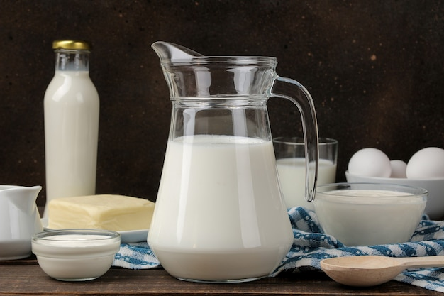 Milk products. milk, sour cream, cheese, butter and cottage cheese on a brown wooden table