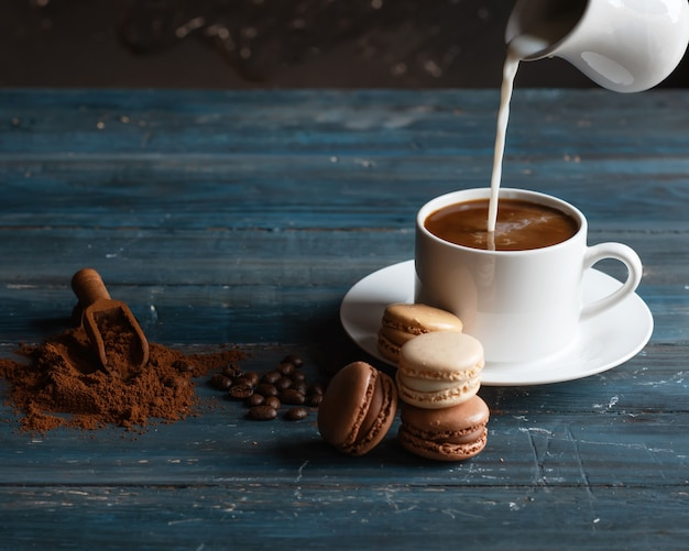 Milk putting on cup of coffee,  coffee beans, ground coffee and macaroons on wooden background