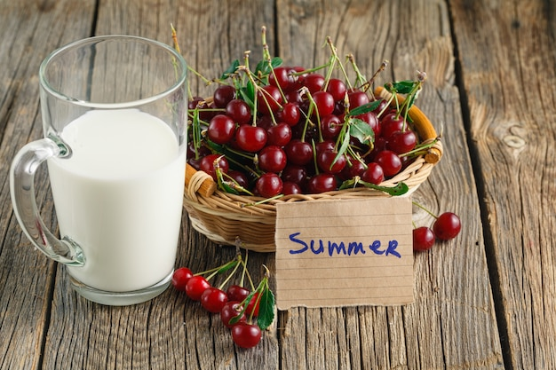 Milk and ripe cherry on a wooden table