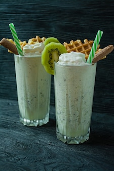 Milk shake with kiwi, ice cream and whipped cream, marshmallows, cookies, waffles, served in a glass cup.