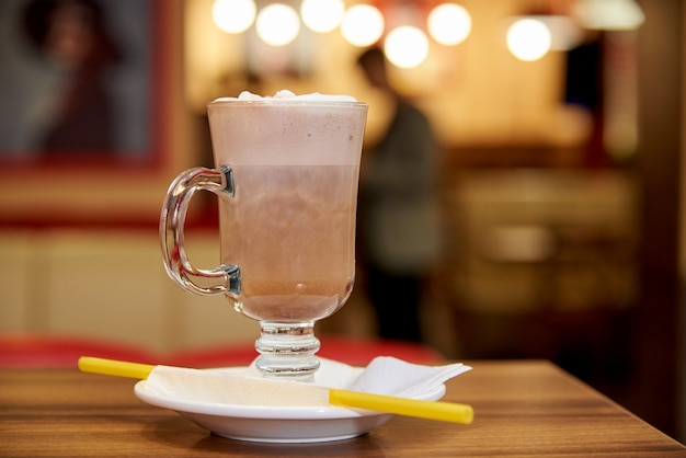 Milk shake with straws on a wooden table in a cafe.