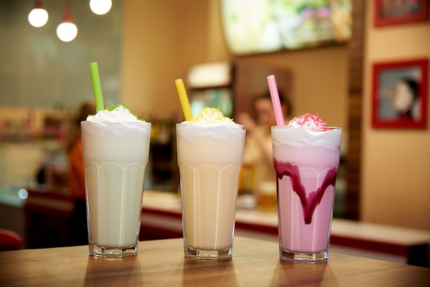 Milk shakes with straws on a wooden table in a cafe.