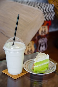 Milk smoothie with coconut cake on glass table