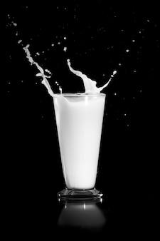 Milk splash with glass on black