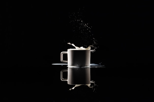 Milk splashes in white cup on black background