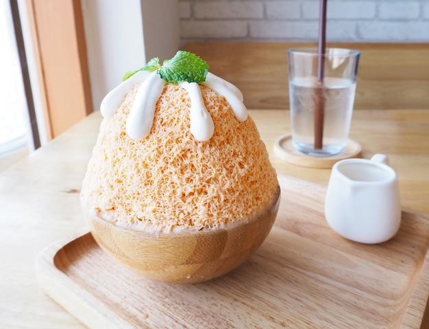 Milk tea bingsu (korean dessert) on wooden plate.