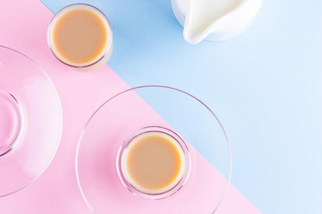 ピンクブルーの背景にミルクティー。トルコのティーカップとミルクジャグ。牛乳と伝統的なイングリッシュブラックティーのカップ。スペースをコピーします。上面図