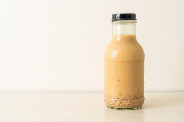 Молочный чай с пудингом желе в стеклянной бутылке на столе
