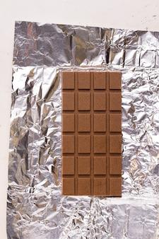 빛나는 호일 배경에 우유 채식 초콜릿입니다. 위에서 보기