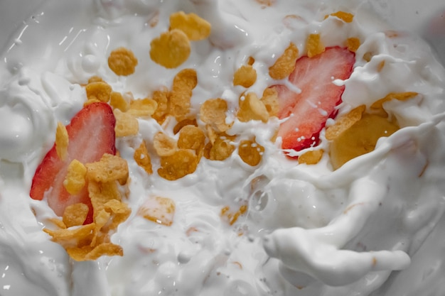 Milk with cereals and fruit splashing waves isolated white background