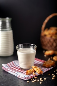 Молоко со свежеиспеченным домашним арахисовым печеньем на темной стене