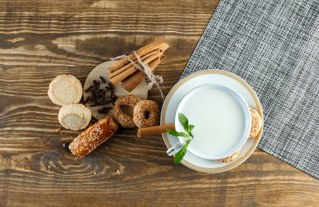 Milk with mint, biscuits, cloves, cinnamon sticks in a cup on wooden surface