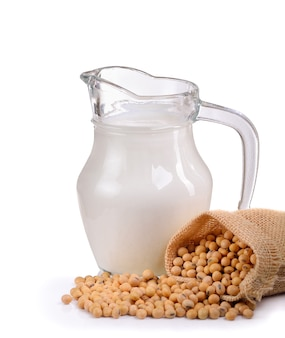 Milk with soy beans on white wall