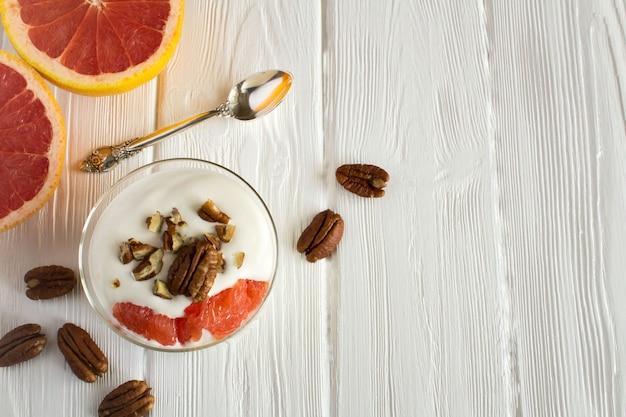 白い木の表面にグレープフルーツとピーカンナッツのミルクヨーグルト。上面図。