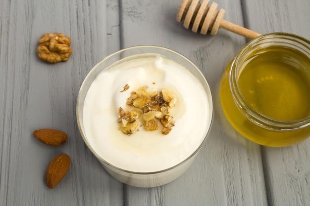 灰色の木製の背景に蜂蜜とナッツのミルクヨーグルト。上からの眺め。