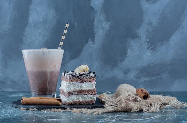 Milkshake, torta e cannella sul bordo, su sfondo blu. foto di alta qualità
