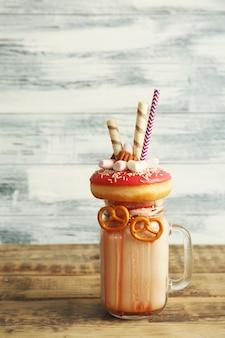 Молочный коктейль, пончик и другие сладости в банке на деревянном столе