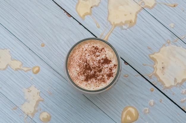 Молочный коктейль с бананом, овсом и корицей в стакане, вид сверху, горизонтальный