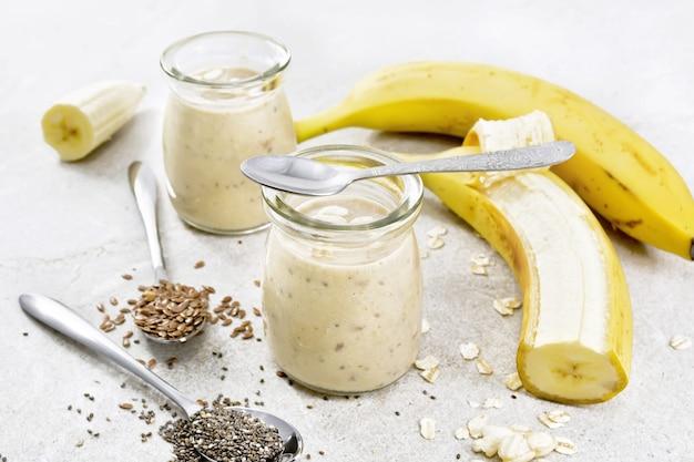 치아 씨앗, 아마 씨앗, 오트밀, 부풀어 오른 쌀과 갈색 돌 테이블 배경에 두 개의 유리 항아리에 바나나와 밀크 쉐이크