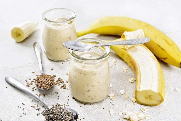 Milkshake with chia seeds, flax seeds, oatmeal, puffed rice and banana in two glass jars on a brown stone table background