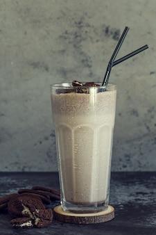 Молочный коктейль с печеньем в высокий стакан.