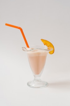 Milkshake with nectarines in a glass with a plastic orange tube in it on a white background. the concept of healthy and delicious food