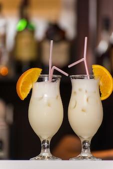 Молочный коктейль с ломтиками апельсина и соломкой.