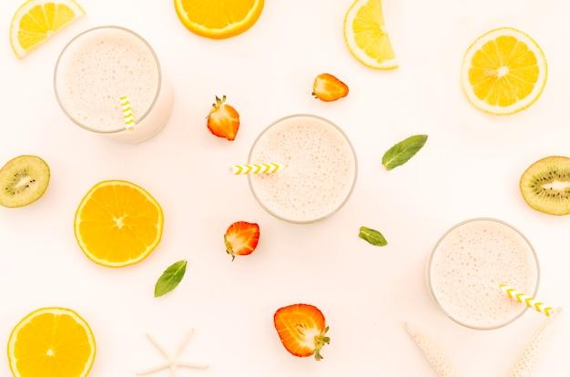 Молочные коктейли с соломкой, нарезанными фруктами и ягодами