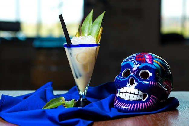 Milky cocktail garnished with pineapple, next to blue mexican skull
