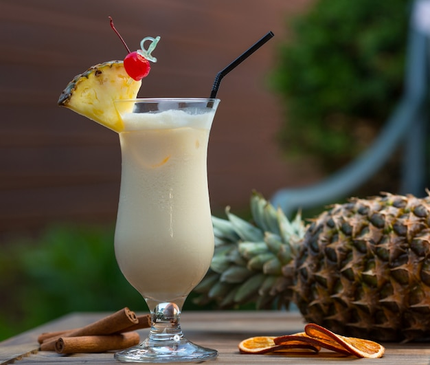 Milky cocktail in glass with pinapple slice and a cherry.