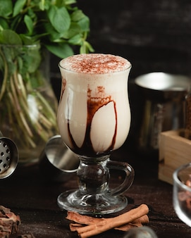 Milky cocktail with chocolate syrup and cocoa powder.