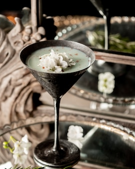 Milky cocktail with chopped coconut inside.