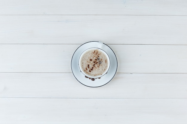 Milky coffee in a cup on a wooden background. top view.