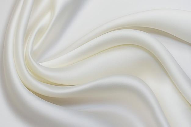 Шелковая ткань молочного цвета в художественной раскладке. текстура, фон, узор.