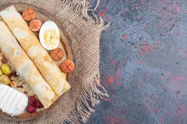 계란과 화이트 치즈를 곁들인 유백색 크레이프.