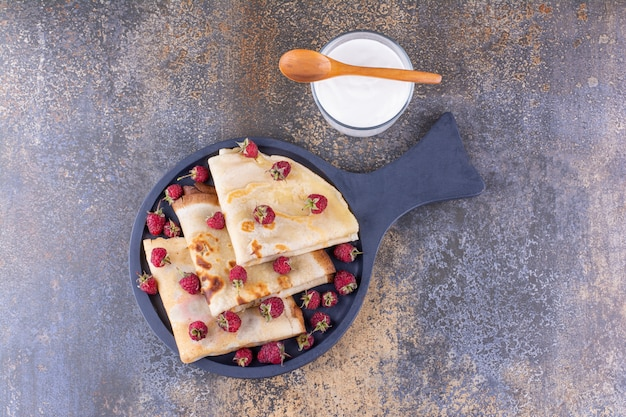 Milky crepes with raspberries on a platter