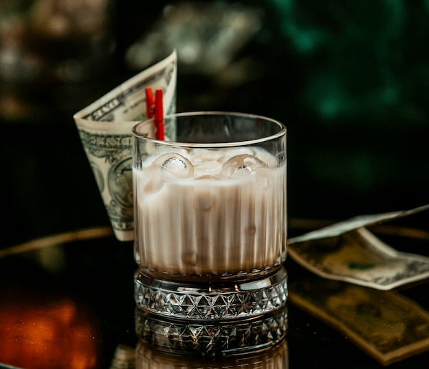 Milky drink with ice cubes in whisky glass pinned with dollar