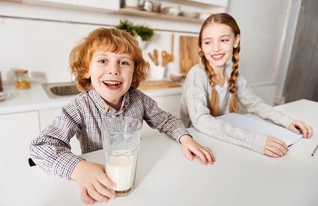 Milky moustache. cheerful charming adorable siblings starting their day together while the boy drinking milk and his sister doing her home assignment
