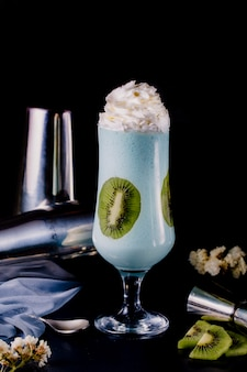 Milky smoothie in a glass with cream and kiwi.