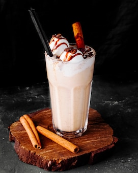 Milky smoothie with icecream balls and cinnamon sticks.