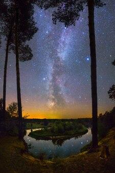강이 있는 아름다운 풍경 위에 은하수와 많은 별