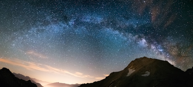 Milky way arch and starry sky on the alps. panoramic view, astro photography, stargazing. light pollution in the valley below.