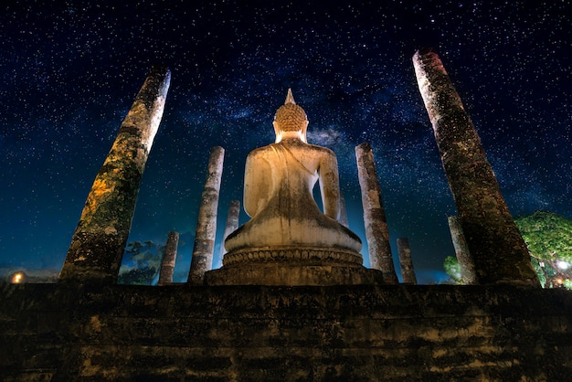 Milky way over big buddha at night in wat mahathat temple, sukhothai historical park, thailand.