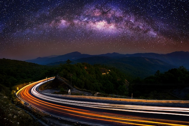 Via lattea e luce auto sulla strada al parco nazionale di doi inthanon nella notte, chiang mai, thailandia.